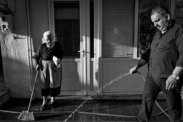 michael coyne documentary photographer and photojournalist: Shopkeepers clean their footpath - Greece