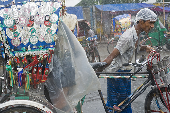 michael coyne documentary photographer and photojournalist: A driver pulls his rickshaw during a rainstorm in Bangladesh