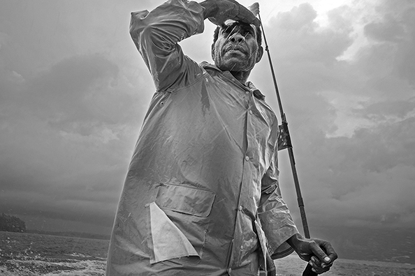 michael coyne documentary photographer and photojournalist: A man steers his boat through a storm - PNG