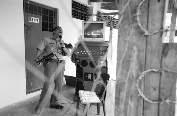 michael coyne documentary photographer and photojournalist: Prison Guard performs karaoke for the prisoners - Philippines