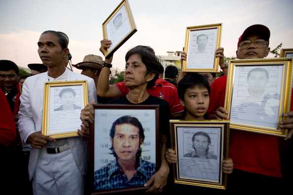 Mourners carry photographs of people killed in a Bangkok massacre - Thailand : michael coyne documentary photographer and photojournalist